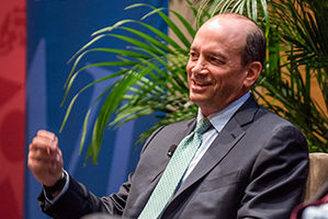 Joel Greenblatt talks to the audience from a chair onstage