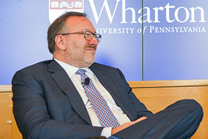 Seth Klarman reclines in a chair on stage in front of a Wharton logo