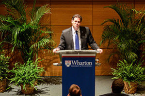 Ron Dermer talks at a Wharton podium with potted plants on the stage behind him