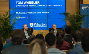 Tom Wheeler and Kevin Werbach sit on a stage with an audience in the foreground
