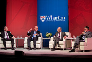 The Wharton Dean and three faculty members sit on a stage, in discussion