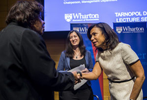 Edith Cooper shaking a woman's hand with Nancy Rothbard behind her