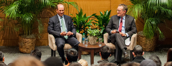Joel Greenblatt and Howard Marks sit in chairs on a stage with Wharton banners behind them and an audience in the foreground