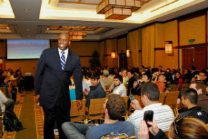 Magic Johnson walks through the aisle of an audience of students