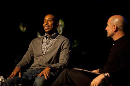Chris Bridges, also known as Ludacris, sits on stage with Bobby Turner