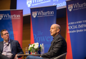 Bobby Turner and Chris Geczy in conversation on a stage surrounded by Wharton banners