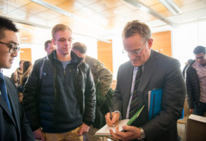 Howard Marks signs a copy of his book for an onlooking student