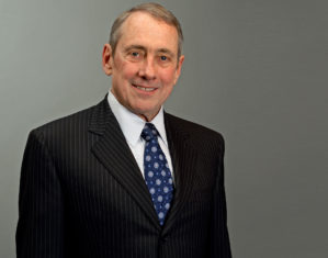 photo of Dr. Marshall Blume, whearing a black suit and blue tie against a grey background