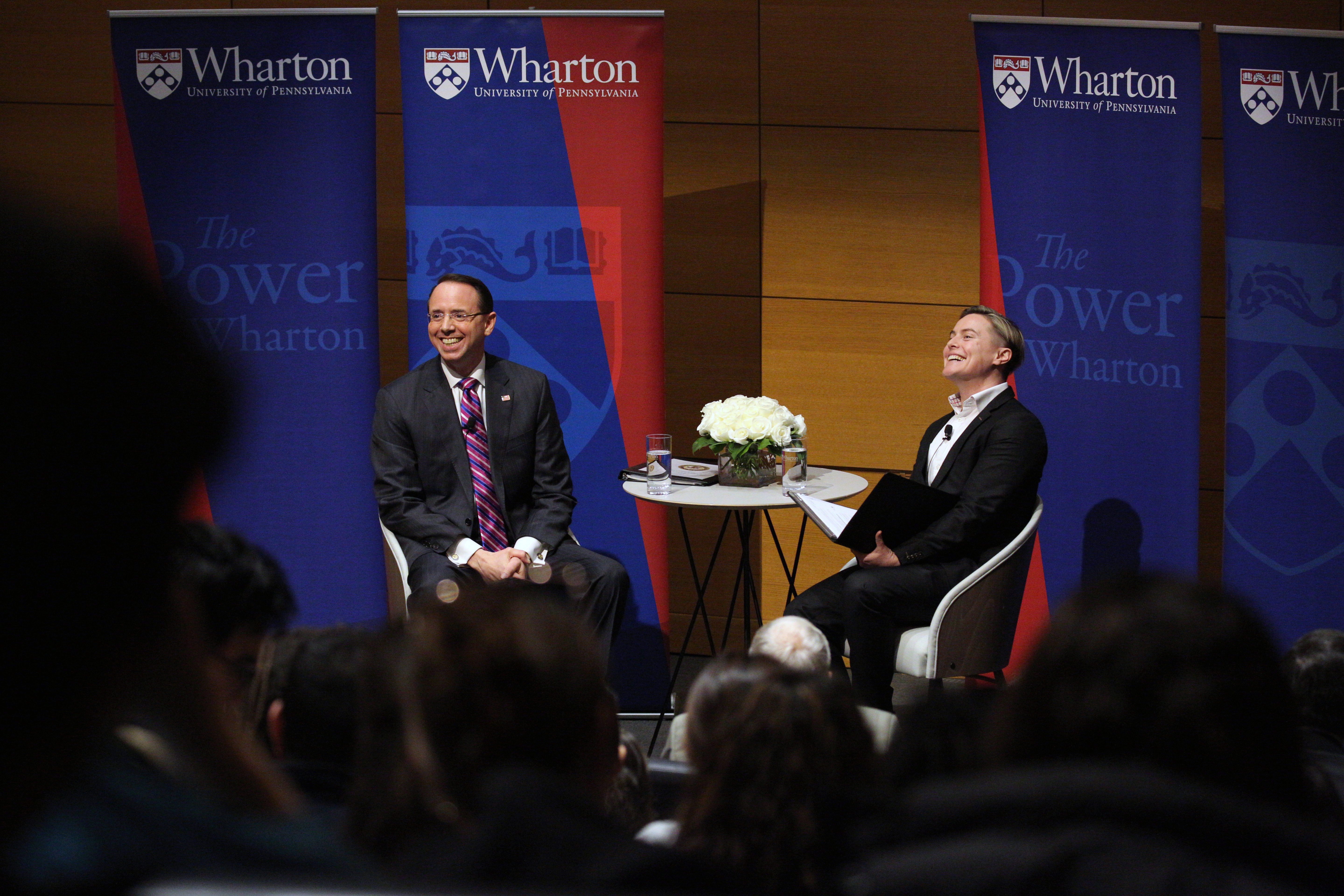 Rod Rosenstein and Amanda Shanor sit on stage, talking to an audience with Wharton signs behind them