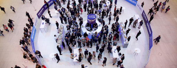 People gather in the center of a very large room, partitioned by Wharton banners with a central circle of food and drinks