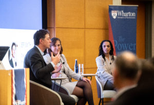 Stephanie Creary, Jeff Smith, and Janet Foutty sit in chairs on a stage, in discussion