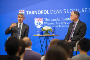 Mohamed A. El-Erian and Dean Geoff Garrett sit on a stage in conversation with an audience in the foreground