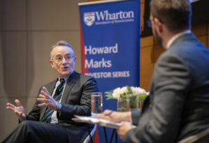 Howard Marks and Chris Geczy in chairs on stage, in discussion